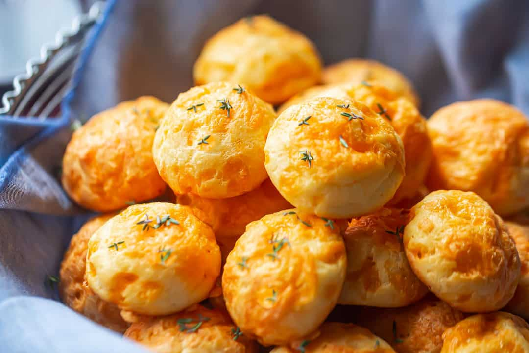Cheese puff recipe prepared and arranged in a basket with fresh herbs.