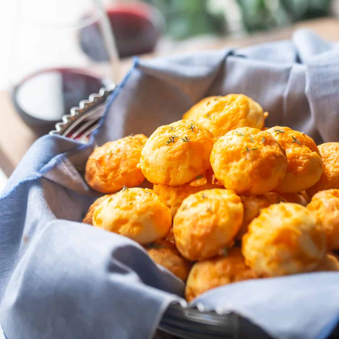 Basket of cheese puffs with glasses of wine in the background.