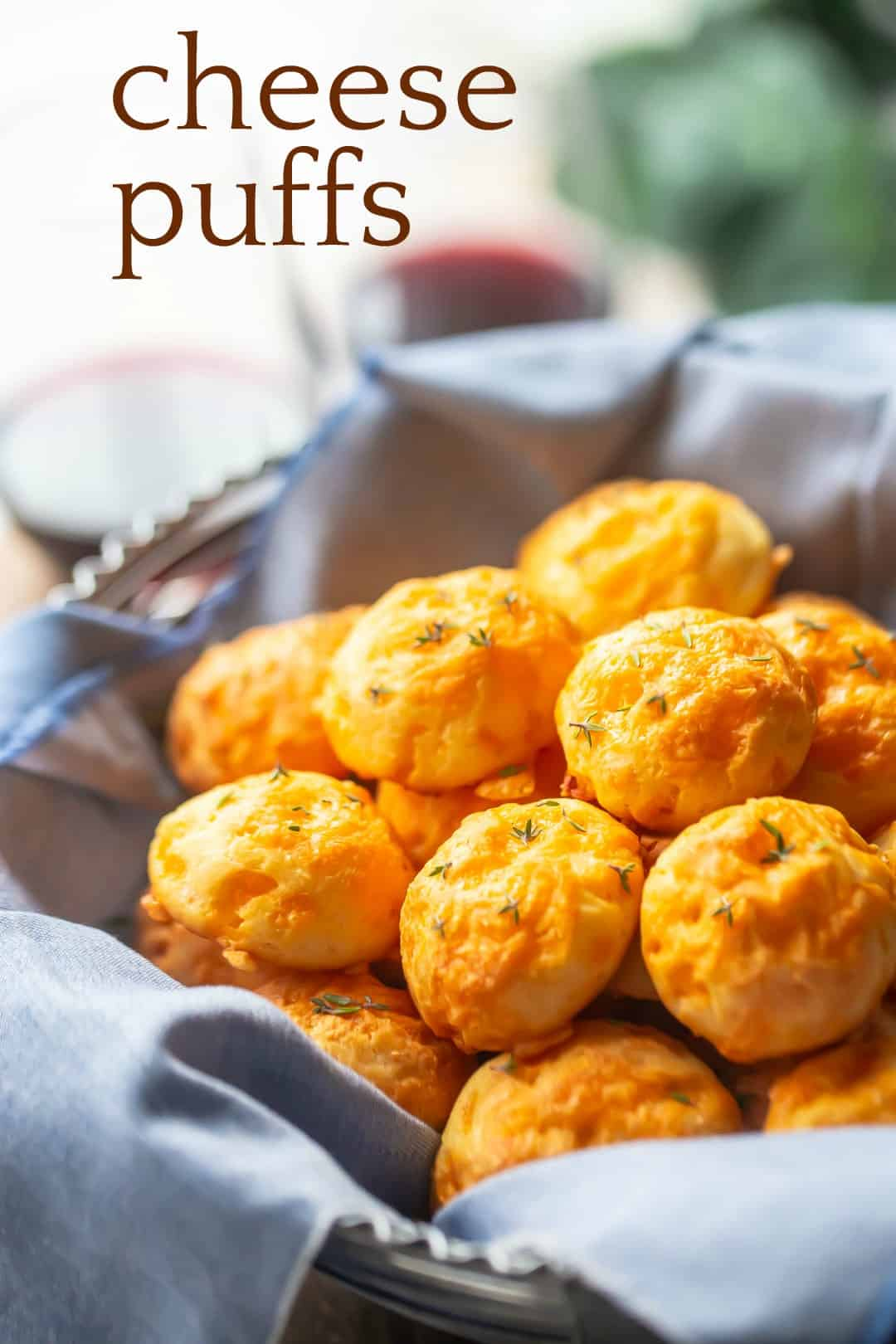 """Gougere in a basket with a blue napkin, with a text overlay above reading """"Cheese Puffs."""""""