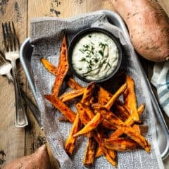 Sweet potato fries on a metal sheet pan with a bowl of creamy dipping sauce.