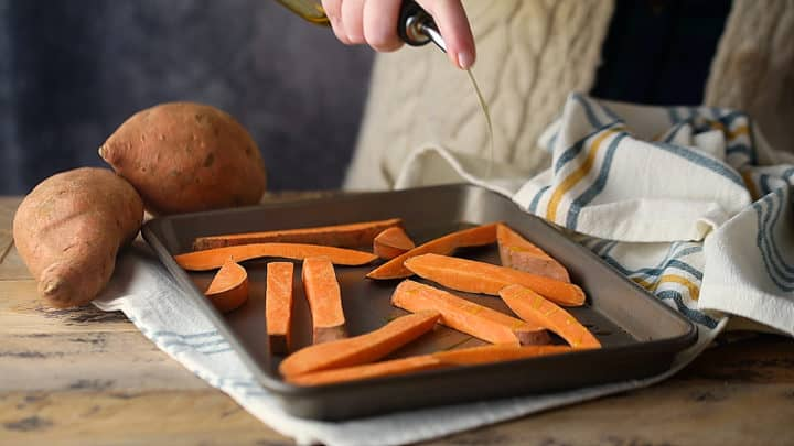 Drizzling cut sweet potatoes with oil.
