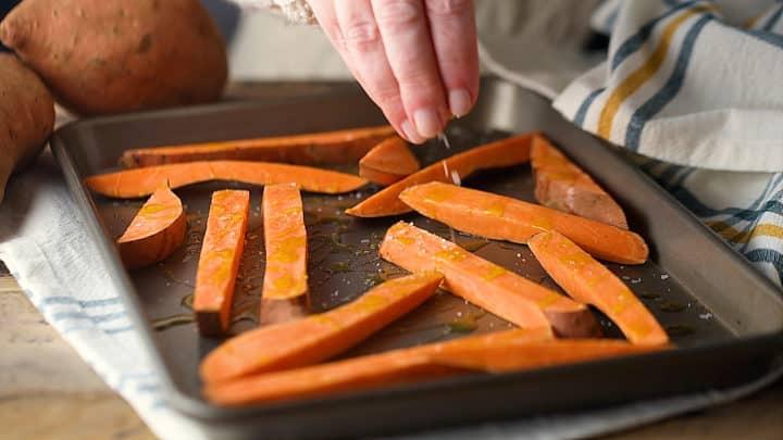 Sprinkling cut sweet potatoes with salt.