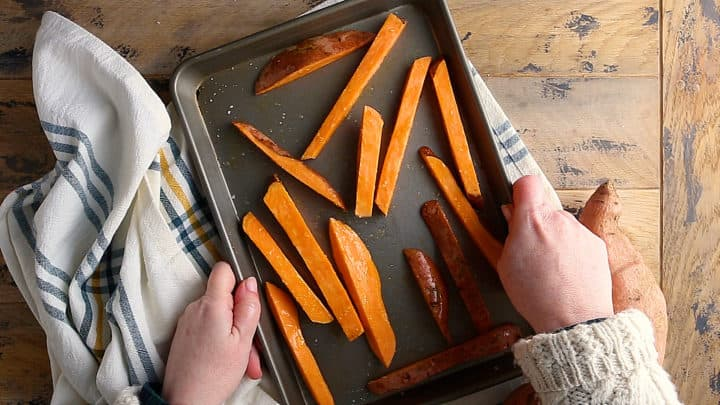 Unbaked sweet potato fries spaced evenly apart so they can crisp in the oven.
