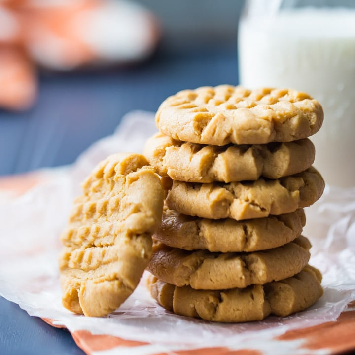 A stack of peanut butter cookies on a napkin, with a bottle of milk in the background.  Cookies are placed on an orange napkin, with a dark blue tabletop below.