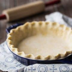 Square image of unbaked pie crust in a dark blue dish with a rolling pin in the background.