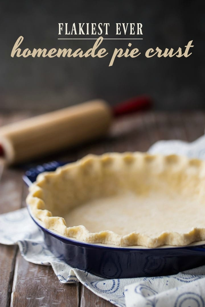 Vertical image of unbaked pie crust in a dark blue dish with a rolling pin in the background and a text overlay.