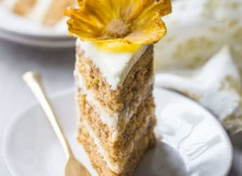 A slice of hummingbird cake with cream cheese frosting and a dried pineapple flower on a white plate.