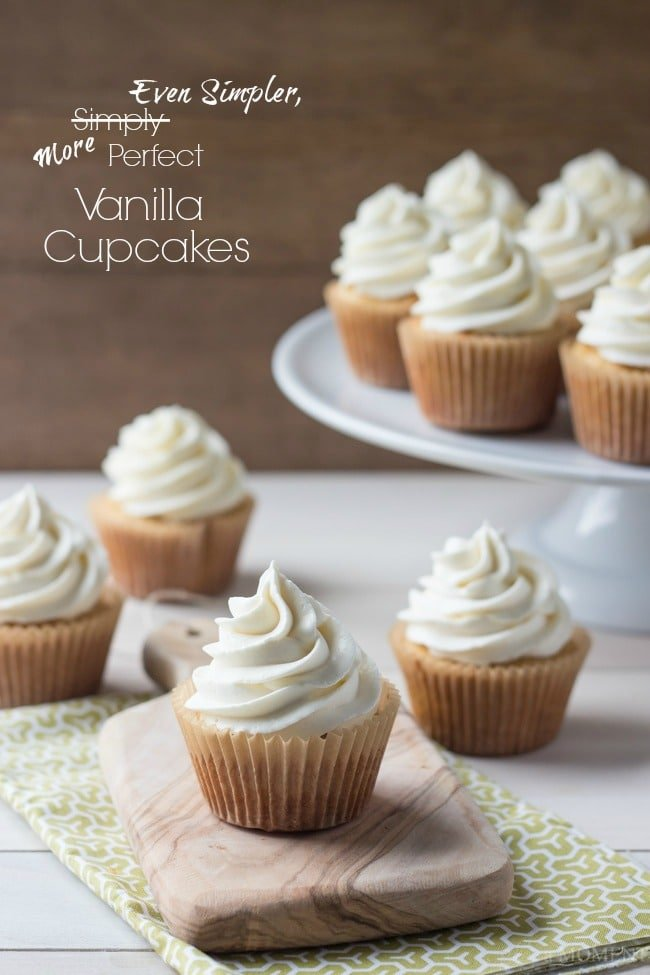 "Vanilla Cupcakes arranged on a wooden board and white pedestal, with a text overlay reading ""Even Simpler, More Perfect Vanilla Cupcakes."""