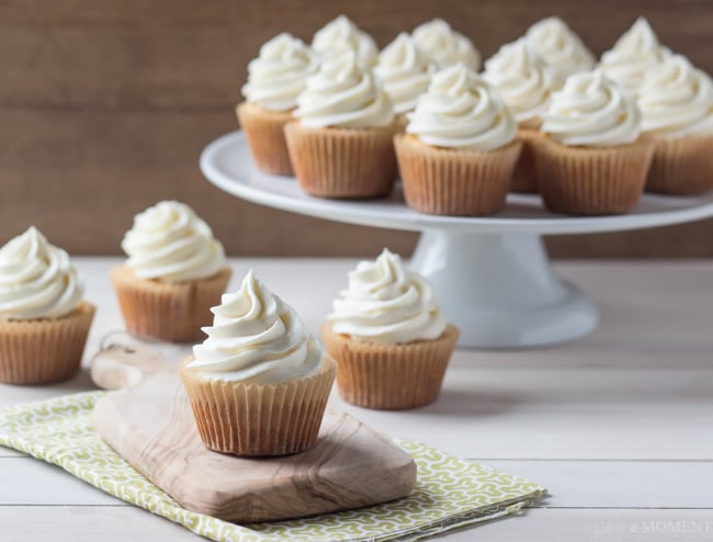 Arrangement of vanilla cupcakes on a white surface with a light wood background.