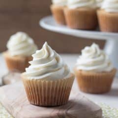 Close up image of a vanilla cupcake with a swirl of buttercream, with a few more vanilla cupcakes in the background.