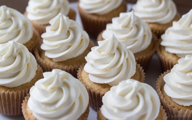 Many vanilla cupcakes with tall swirls of whipped cream.