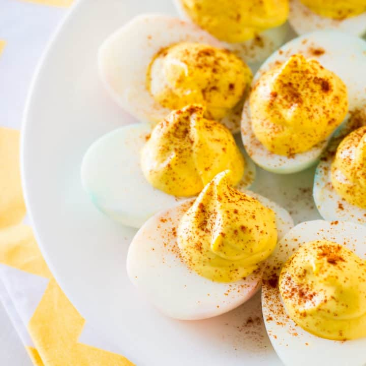 Classic deviled eggs on a white plate with a yellow napkin.