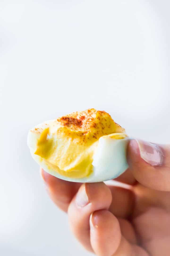 A bitten deviled egg held in hand.