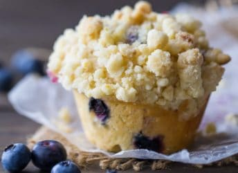 Square image of a bakery-style blueberry muffin with streusel crumb topping on a dark wood background with fresh blueberries scattered around.