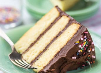 Yellow cake recipe, baked in 3 layers, frosted with chocolate buttercream, and served on a pale green plate.