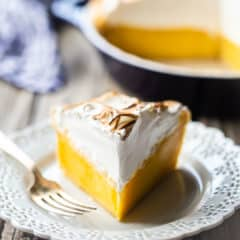 Lemon meringue pie on a lacy white plate.