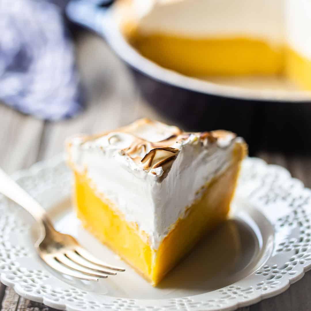 Lemon meringue pie on a lacy white plate.