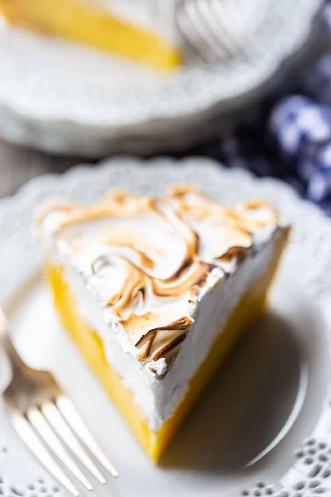 Lemon meringue pie slice on a plate with a blue checked cloth.