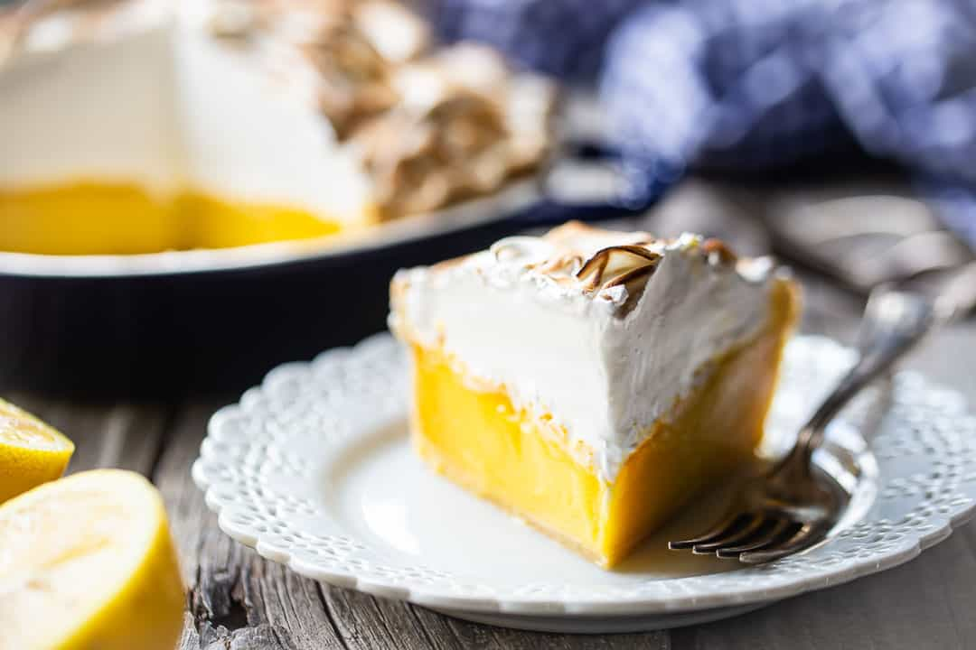Easy lemon meringue pie served on a plate with a blue checked cloth in the background.