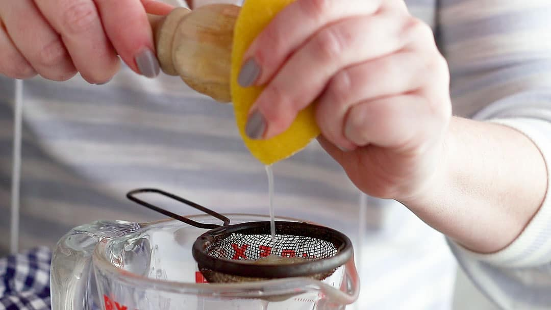 Juicing fresh lemons through a sieve and into a measuring cup.