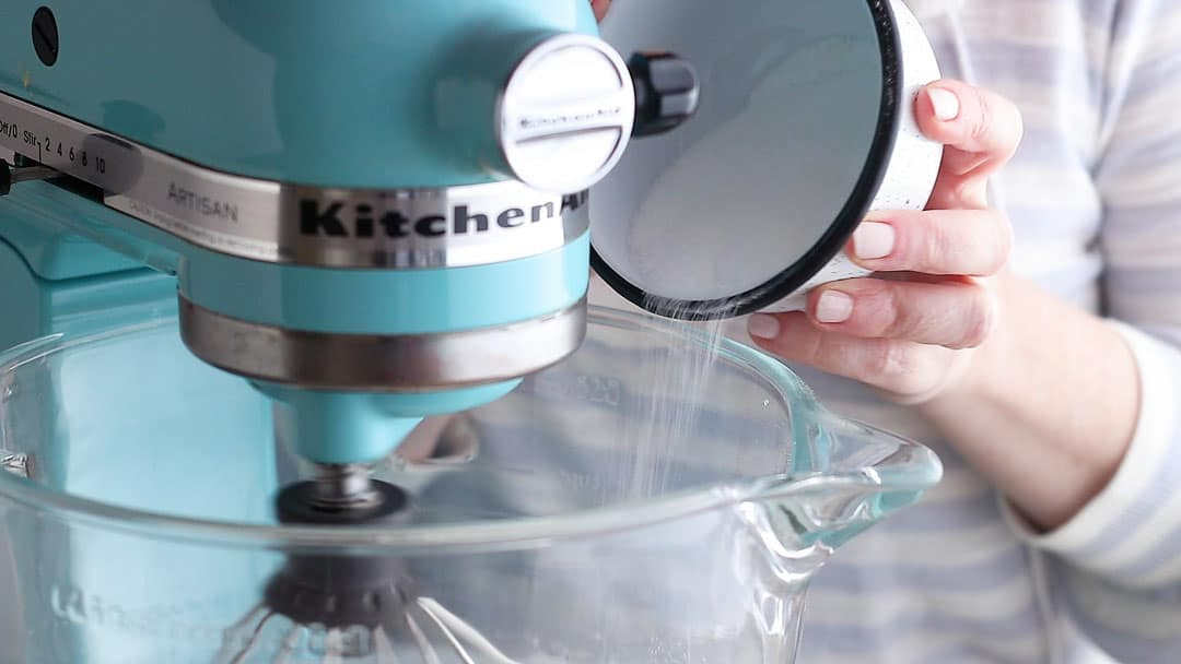 Adding sugar and cornstarch to meringue in a slow, steady stream.