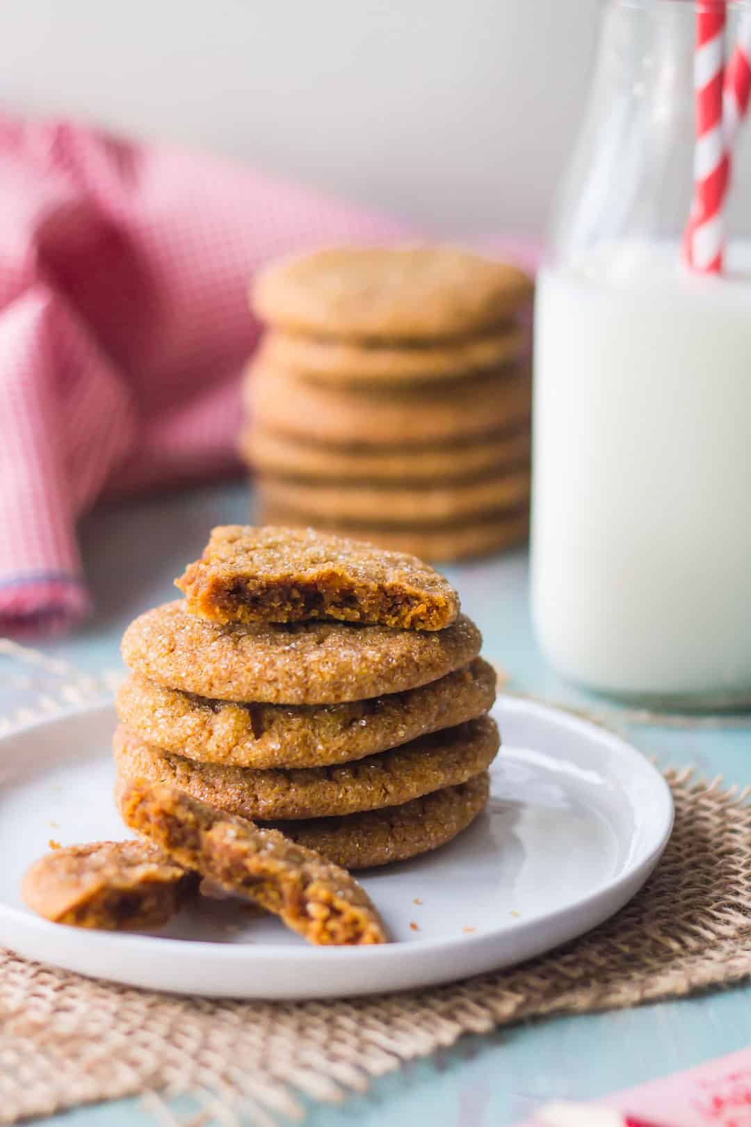 Stack of ginger molasses cookies on a white plate, with a bottle of milk in the background and a red checkered napkin.