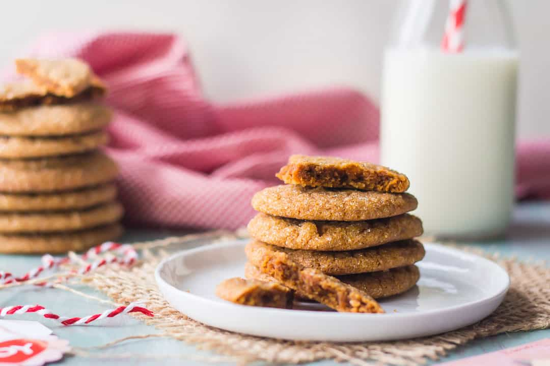 Ginger cookies stacked on a plate with a bottle of milk in the background and a spool of red and white baker's twine.