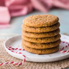 A stack of soft ginger cookies on a small white plate with red and white baker's twine.