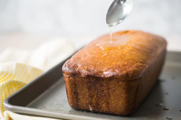Drizzling lemon syrup over loaf cake.