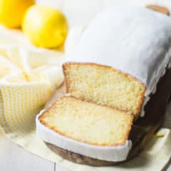 Iced lemon loaf on a wood cutting board with lemons in the background.