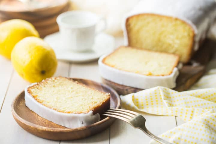 Horizontal shot of iced lemon cake on a wooden board with lemons and teacups in the background.
