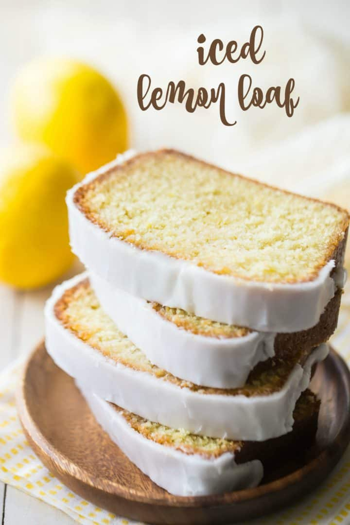 "Slices of lemon loaf cake stacked on a wooden plate, with a text overlay reading ""Iced Lemon Loaf."""