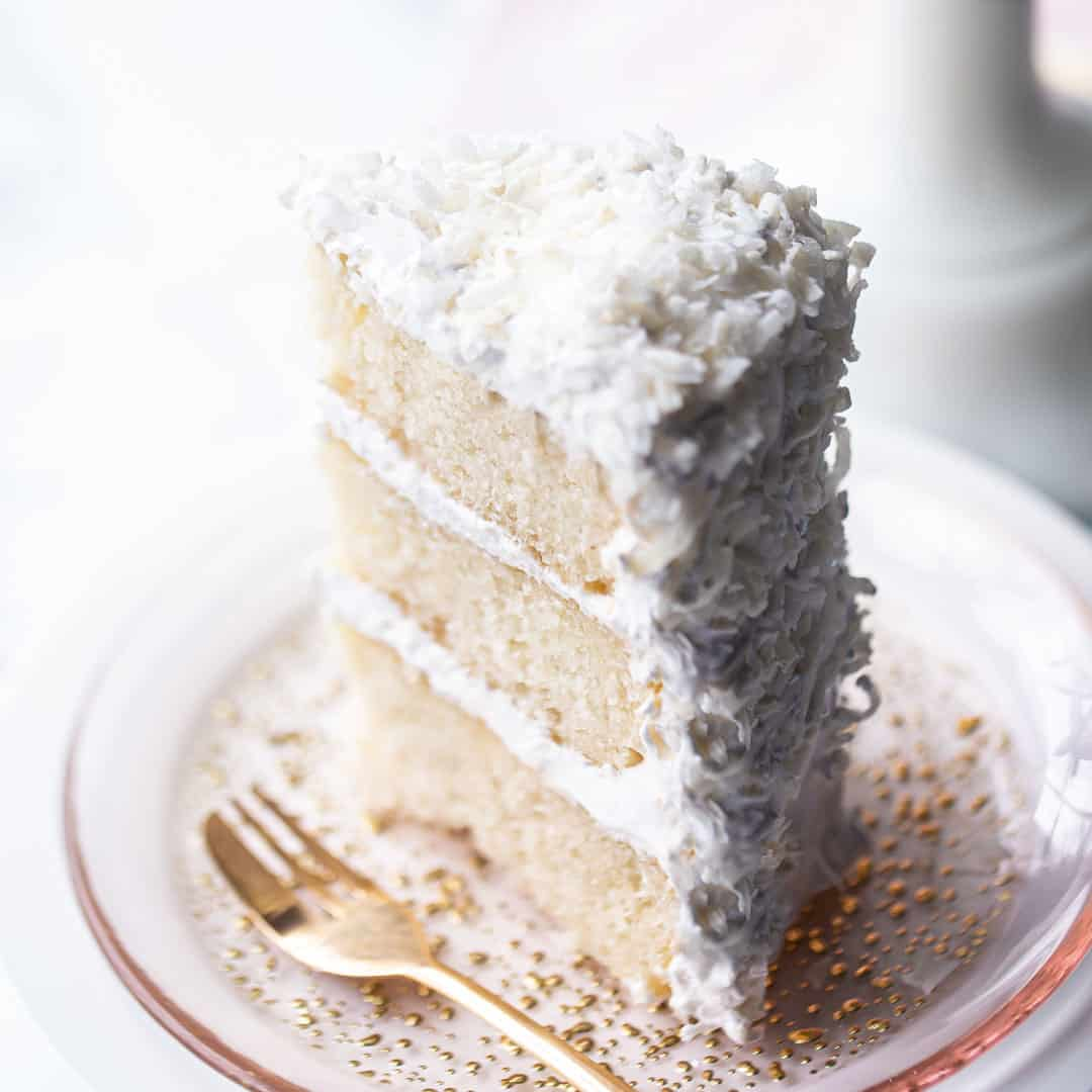 Tall slice of coconut cake on a pink plate with a gold fork.