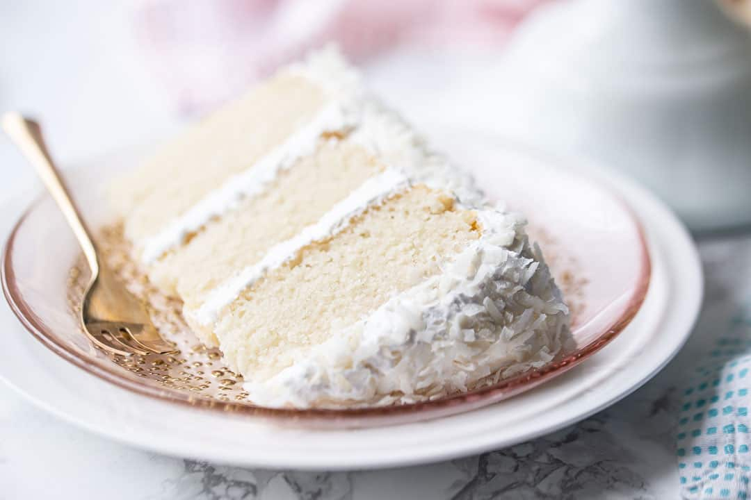 Best coconut cake recipe, baked and frosted with marshmallow frosting and coconut, sliced and served on its side.