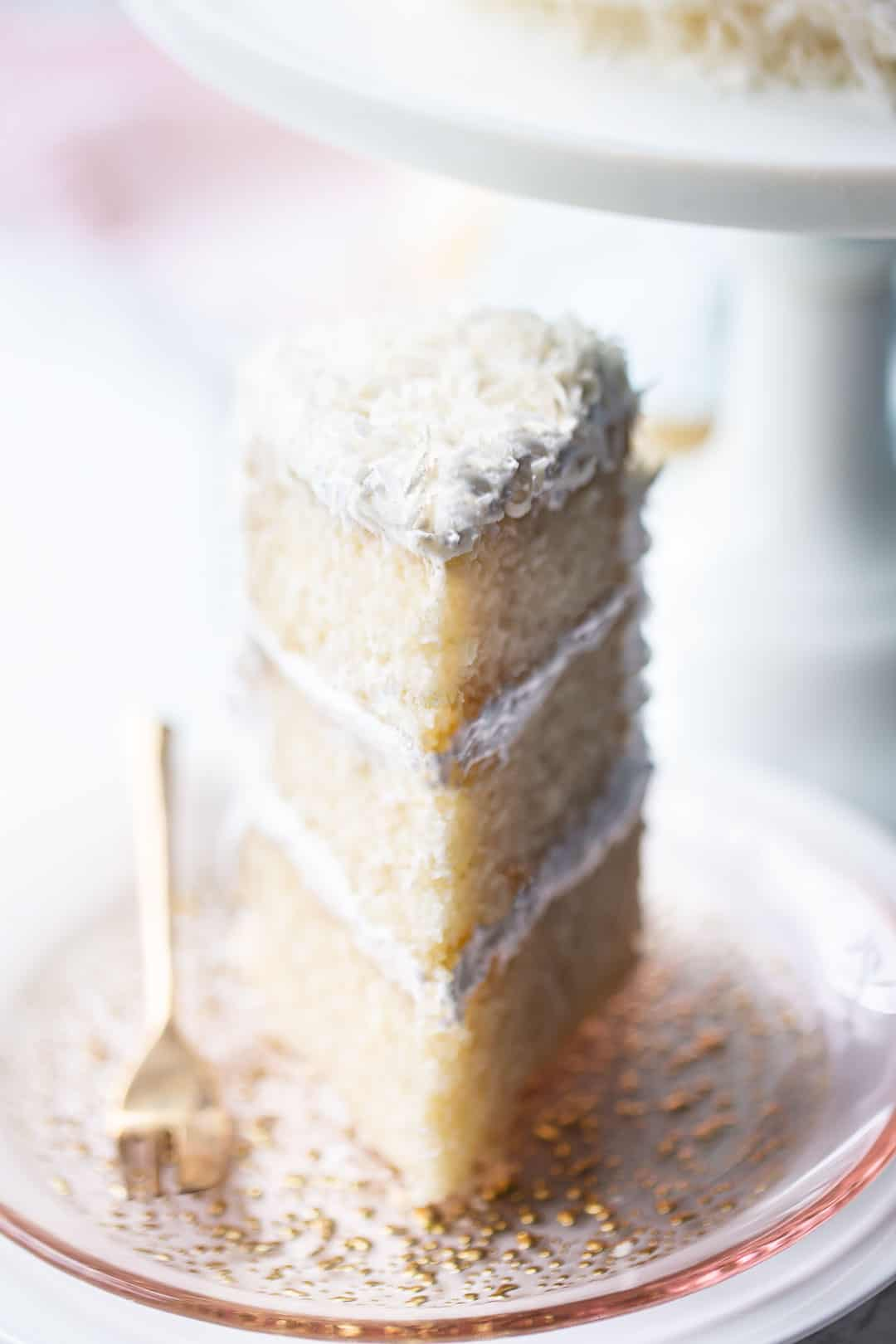 Tall wedge of coconut cream cake, served on a pink glass plate with a white pedestal in the background.