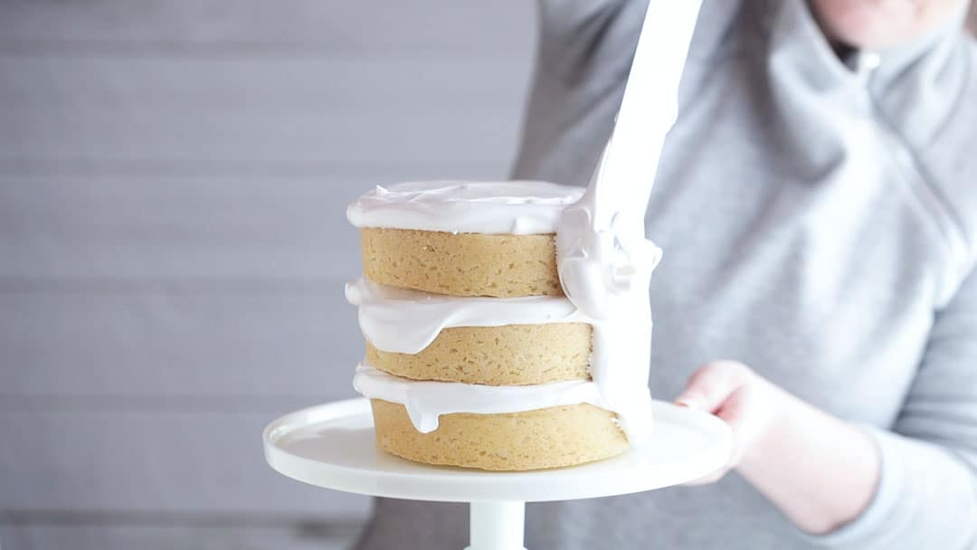 Icing a coconut layer cake with marshmallow frosting.