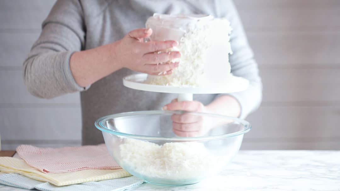Coating a frosted cake in dessicated coconut.