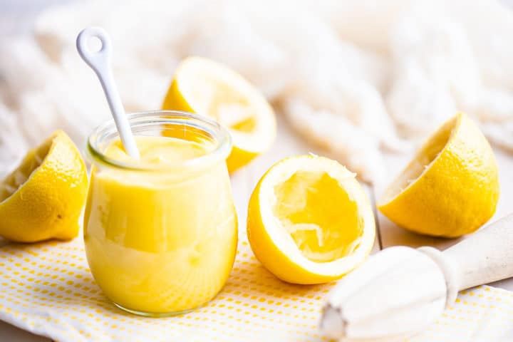 Small jar of homemade lemon curd with a white ceramic spoon.