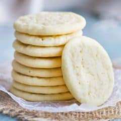 A stack of homemade chewy sugar cookies on a pale blue background.