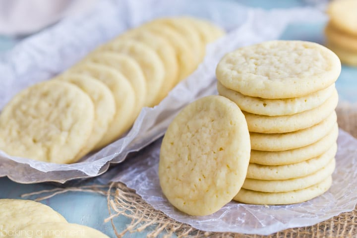 Horizontal image of a stack of easy sugar cookies, with a tray of more cookies in the background.