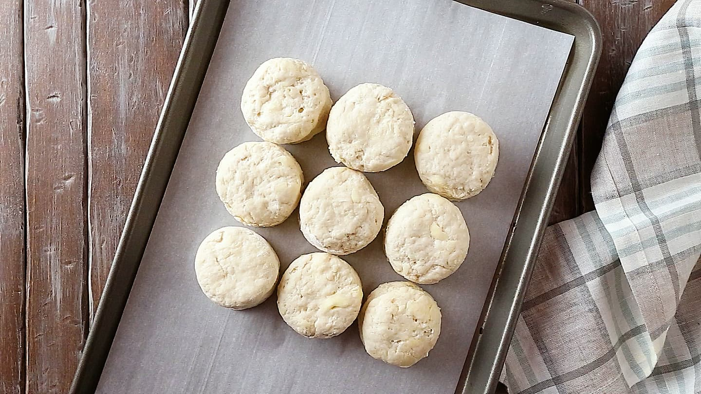 Homemade biscuits on a parchment-lined baking sheet.