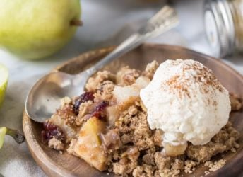 Pear cranberry crisp: a comforting cool-weather dessert! Sweetened with maple syrup, spiked with warm ginger, and topped with a buttery oatmeal pecan crumb.