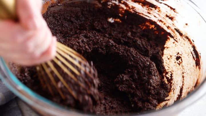 Mixing sugar, cocoa, and melted butter together to make brownies from scratch.