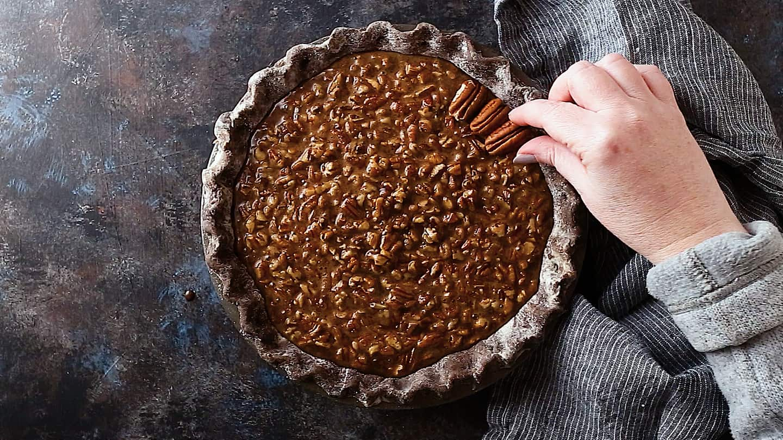 Garnishing chocolate pecan pie with pecan halves.