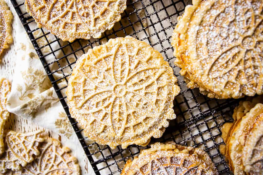 A freshly made batch of crisp, perfect pizzelles, cooling on a baker's rack, garnished with powdered sugar.