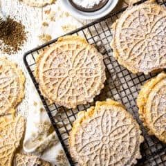 Overhead image of pizzelle on a wire cooling rack with whole anise seeds and powdered sugar.