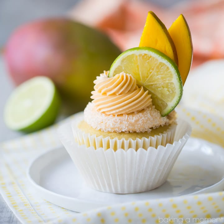 Mango Margarita Cupcakes: a yellow mango and lime cupcake with a salted rim and a swirl of mango margarita buttercream on top, garnished with lime and sliced mango