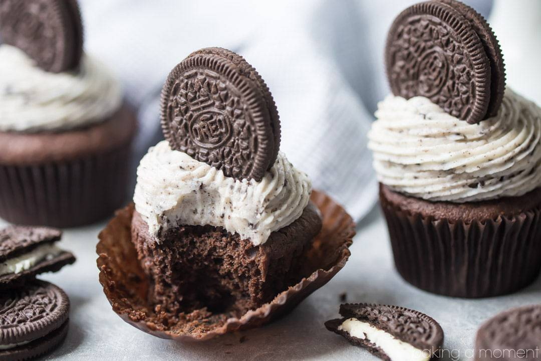 Chocolate Cupcake with Cookies and Cream Frosting and an Oreo Cookie on top, with more cupcakes in the background and stacks of cookies scattered around.