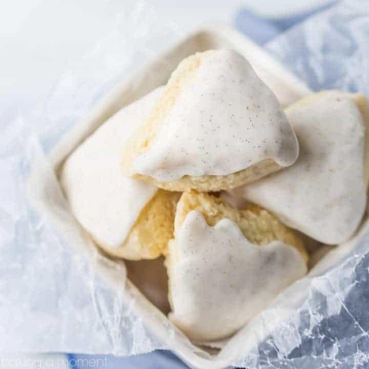 Glazed petite vanilla bean scones in a basket on a blue cloth.  food breakfast brunch