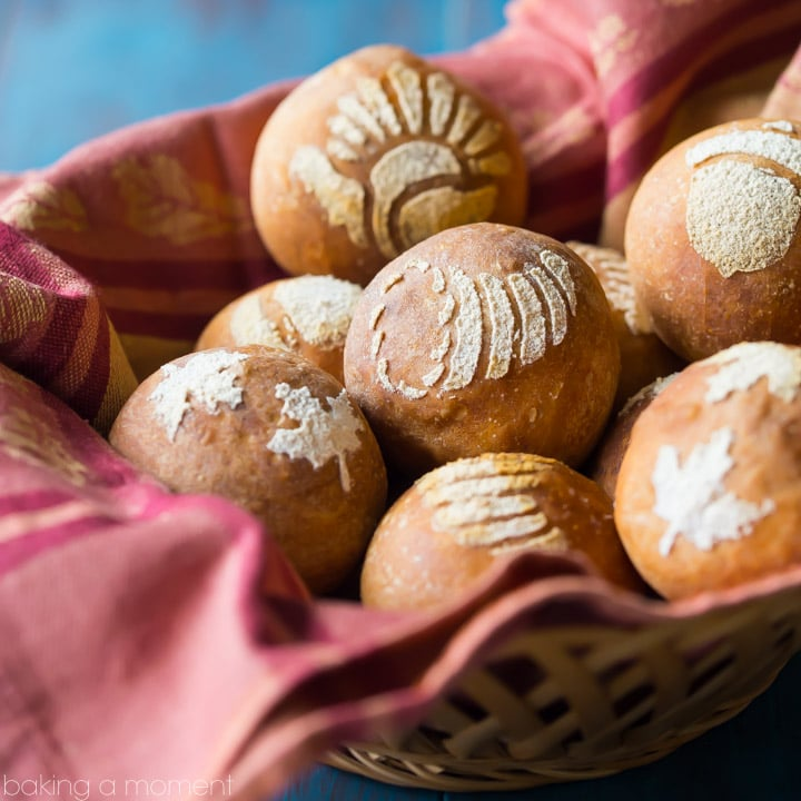Basket lined with a red cloth, filled with bread rolls stenciled with fall/Thanksgiving themed images, on an aqua tabletop. food bread crafts